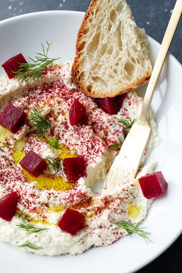 Butter knife in a bowl of whipped almond dip, with olive oil, pickled beets, dill and a slice of sourdough.