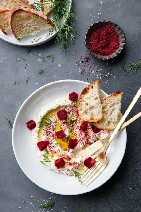 Overhead shot with bowl of whipped almond dip, gold utensils, and bowl of sumac and beet powder and fresh sourdough slices.