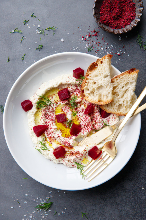 Overhead white bowl with a swirl of whipped almond dip, drizzled with olive oil and topped with cubes of pickled beets and fresh dill.