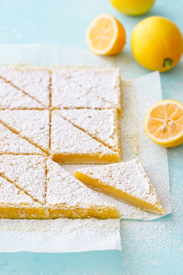 Sliced Meyer Lemon Bars on a light turquoise background with whole and halved Meyer lemons.