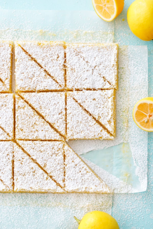 Meyer Lemon Bars on a turquoise background, cut into triangles and dusted with powdered sugar