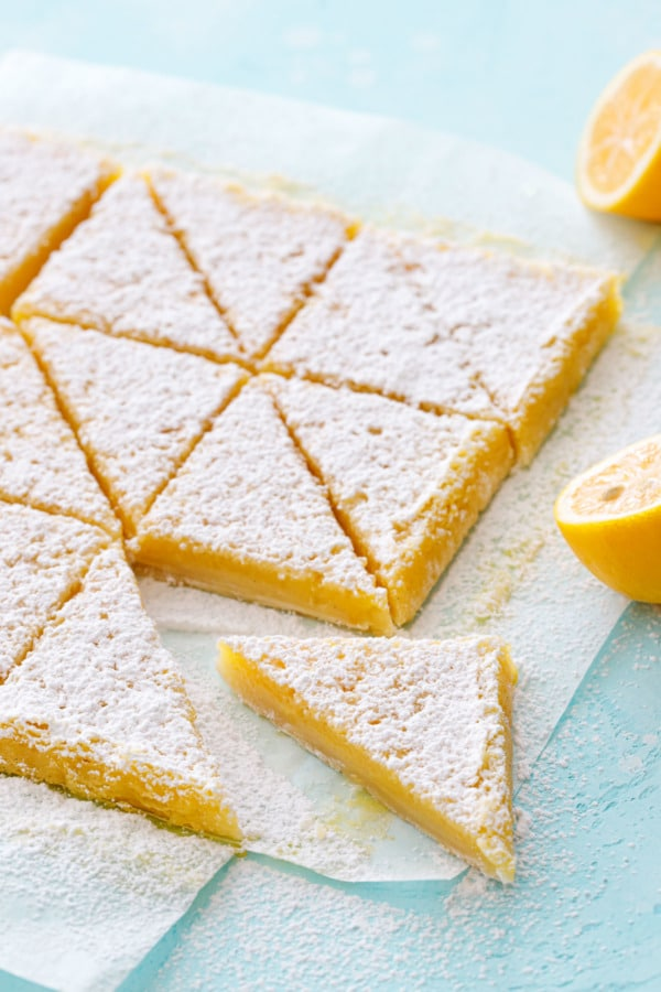 Triangular-sliced Meyer Lemon Bars on a turquoise background.