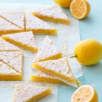 Stacks of sliced Meyer Lemon Bars on a turquoise background, with whole and half Meyer lemons