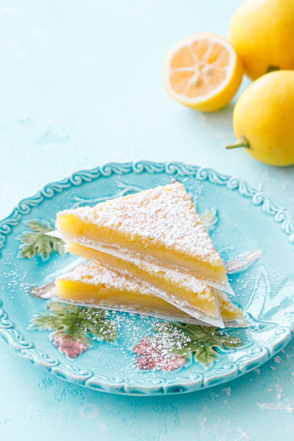 Stack of three triangular-sliced Meyer Lemon Bars on a turquoise plate