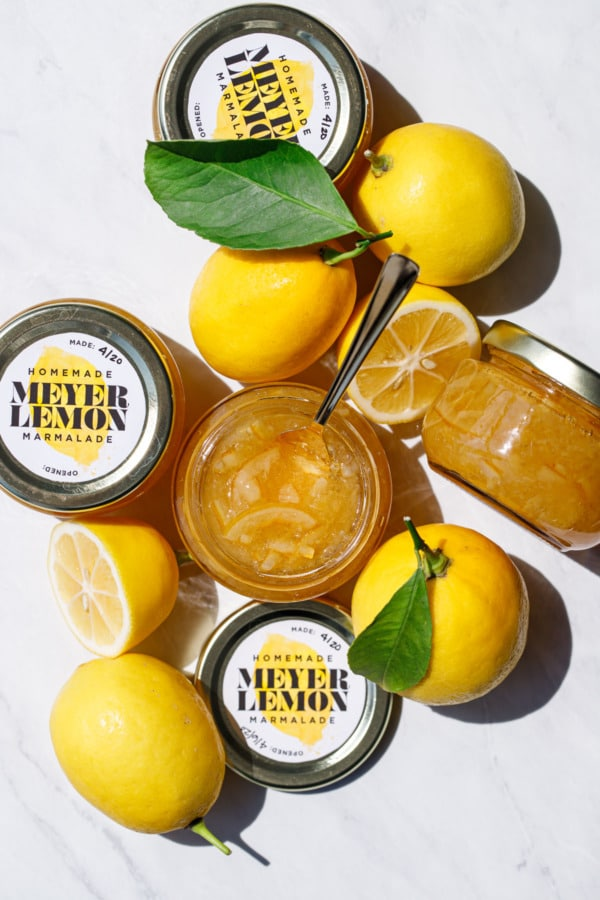 Overhead of jars of Old-Fashioned Meyer Lemon Marmalade and whole/halved lemons with leaves.