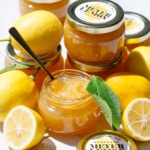 Open jar of Old-Fashioned Meyer Lemon Marmalade, with whole and half lemons and full jars with printable labels.