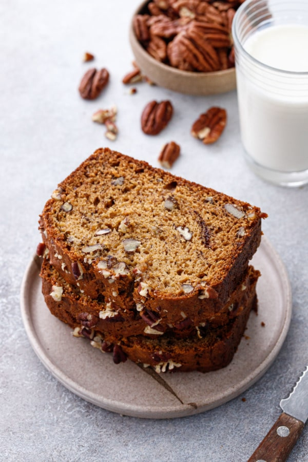 Stack of Bananas Foster Banana Bread slices on a ceramic plate, with glass of milk and bowl of pecans