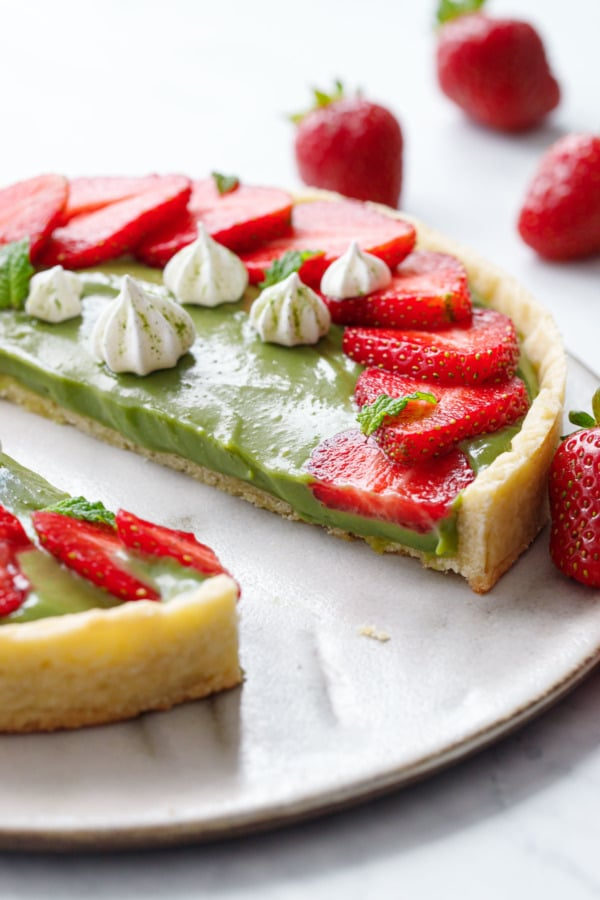 Matcha Strawberry Tart sliced in half to show the texture of the pastry cream filling.