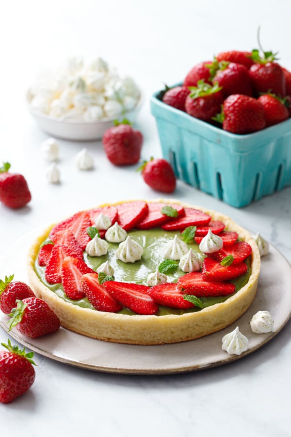 Matcha Strawberry Tart on a marble background, with turquoise basket of strawberries and a bowl of mini meringue kisses.