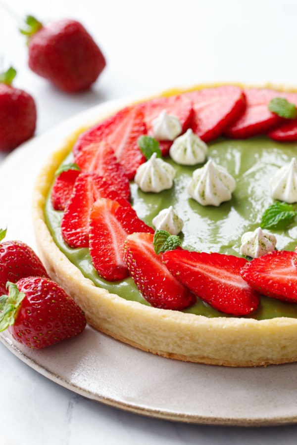 Closeup of green matcha cream filled tart with slices of strawberries arranged in a ring on top, with tiny meringue kisses and fresh strawberries scattered around.