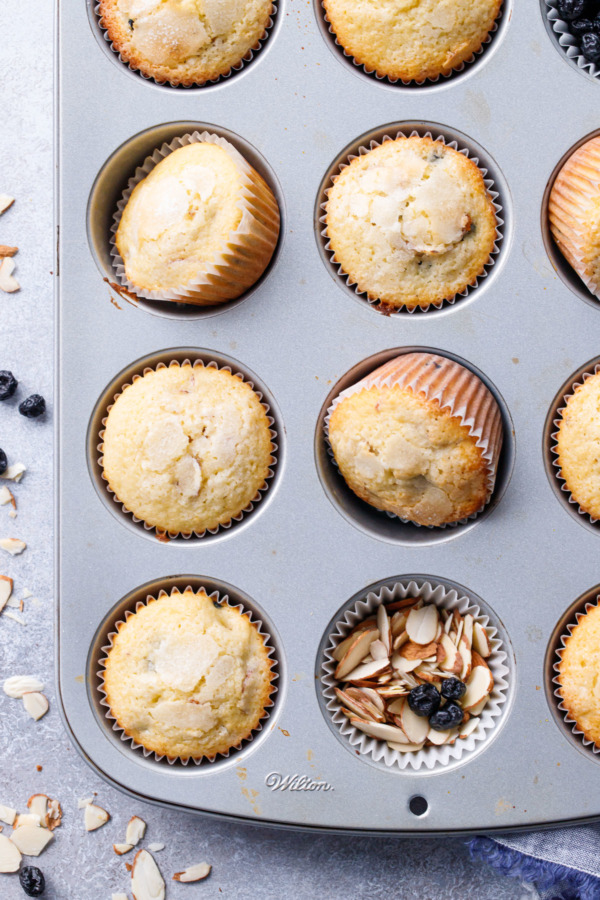 Muffin Tin with Sourdough Muffins with one cup filled with sliced almonds