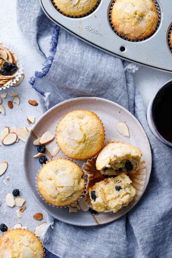 Overhead of plate of Sourdough Muffins with Blueberries and Almonds, linen napkin and muffin tin