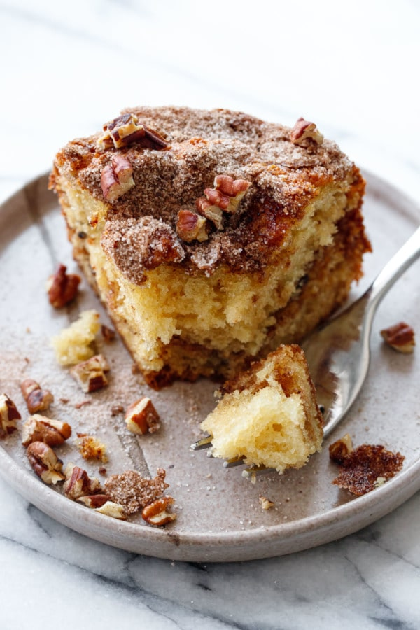 Fork with a bite of coffee cake on a ceramic plate with chopped pecans scattered around