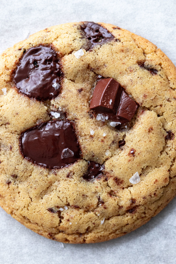 Closeup of Olive Oil Chocolate Chip Cookie, showing flaky sea salt and puddles of melty chocolate.
