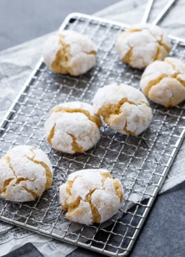 Powdered-sugar coated crinkle cookies on a wire rack, on newsprint parchment on a dark background.