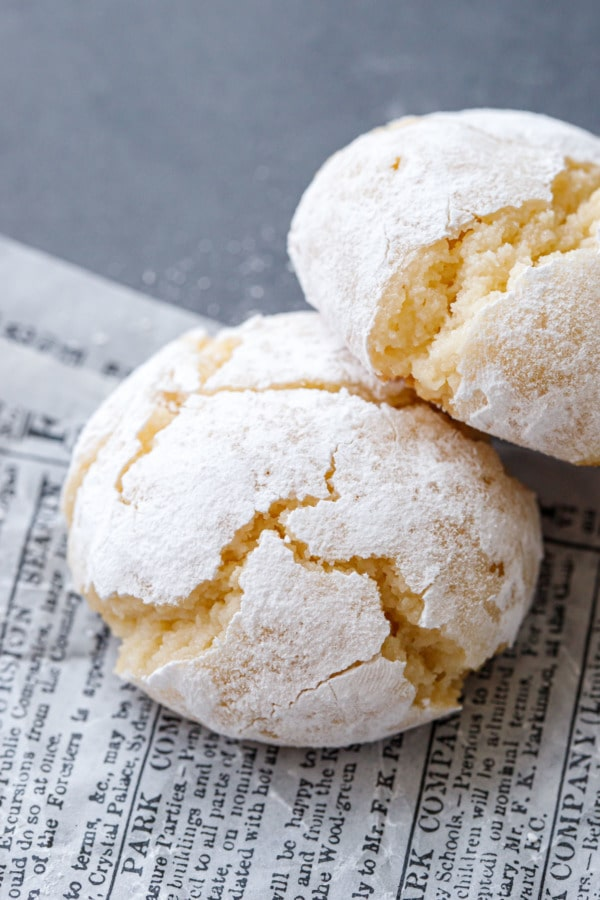 Closeup of two amaretti cookies, coated with powdered sugar with cracks from baking.