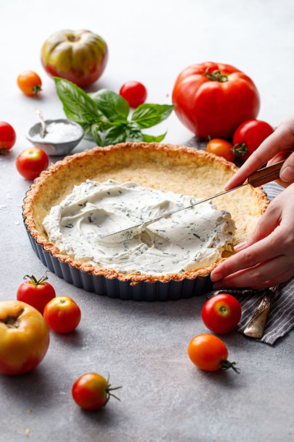 Spreading basil goat cheese into a pre-baked tart shell, surrounded by heirloom tomatoes