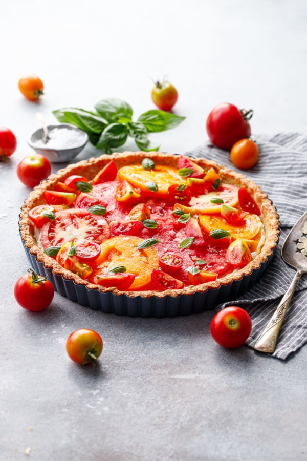 Heirloom tomato and goat cheese tart on a gray background surrounded by heirloom tomatoes