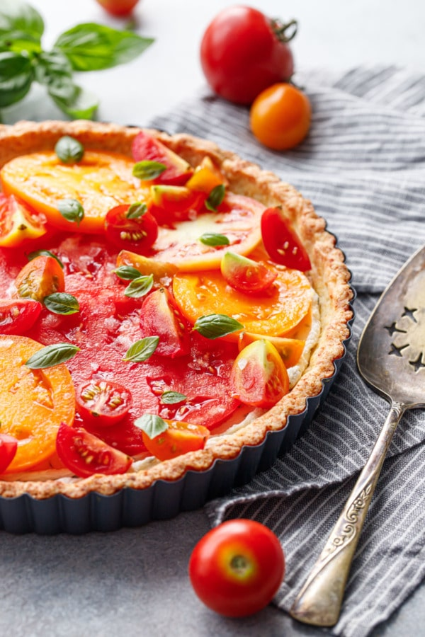 Goat Cheese & Heirloom Tomato Tart with a gray striped linen and vintage silver pie server