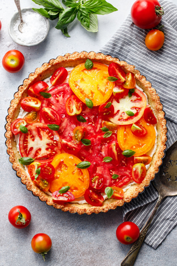 Overhead shot of heirloom tomato tart on a gray background, with tomatoes scattered around and a small bowl of flaky sea salt