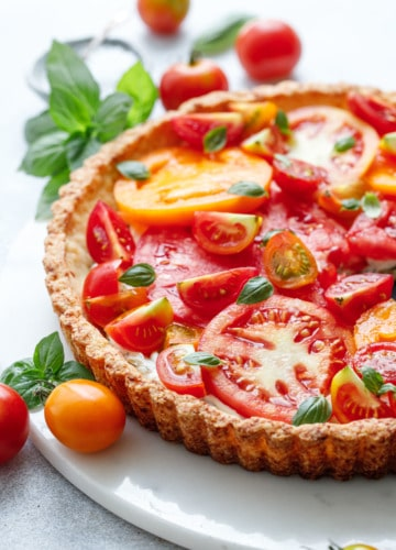 Goat Cheese & Heirloom Tomato Tart on a marble plate surrounded by more tomatoes