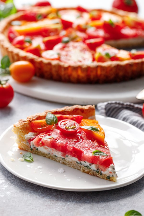 Slice of heirloom tomato tart showing the layers of tomato, goat cheese, and parmesan crust.