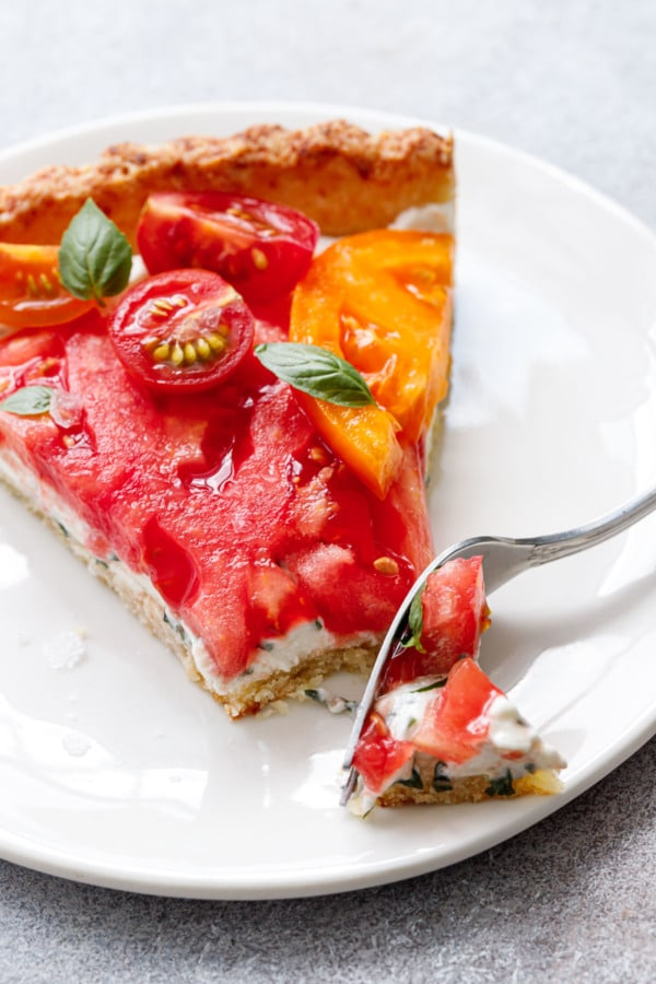 Fork cutting a bite out of a slice of heirloom tomato tart on a white plate