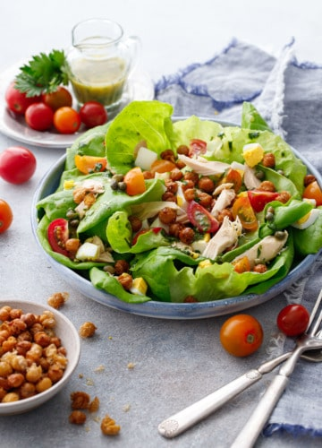 Large shallow dish with butter lettuce and nicoise salad toppings, with a dish of crispy chickpeas and tomatoes and dressing in the background.