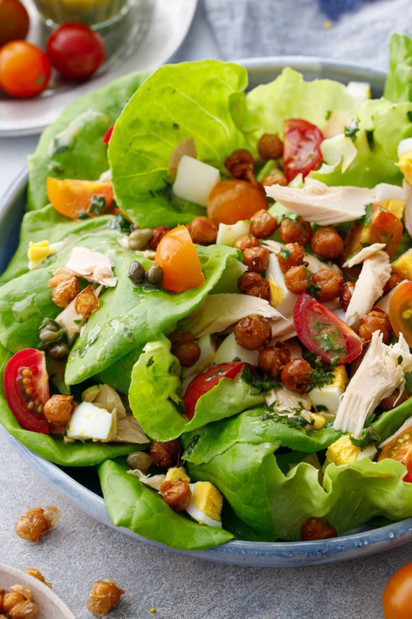 Closeup of salad, butter lettuce topped with tuna, red and yellow cherry tomatoes, hard-boiled egg, crispy chickpeas and a caper vinaigrette dressing.