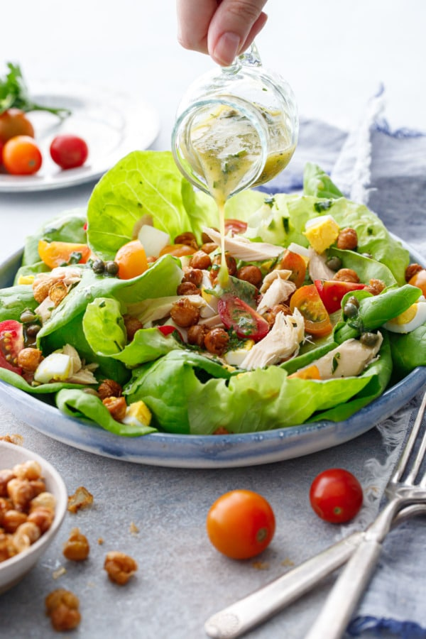 Hand pouring dressing out of a small glass pitcher onto a shallow dish with large leaves of butter lettuce and nicoise toppings.