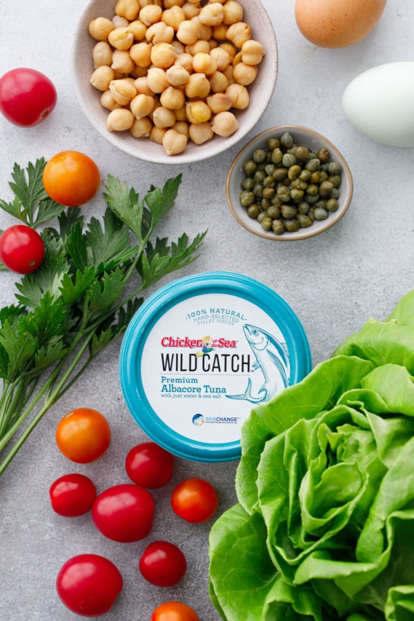 Overhead of the ingredients used in this recipe, including a tub of albacore tuna, butter lettuce, red and yellow cherry tomatoes, fresh parsley, capers, and chickpeas.