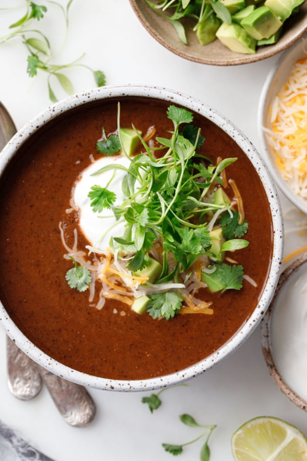Closeup overhead of black bean soup, topped with cheese, sour cream, and cilantro microgreens