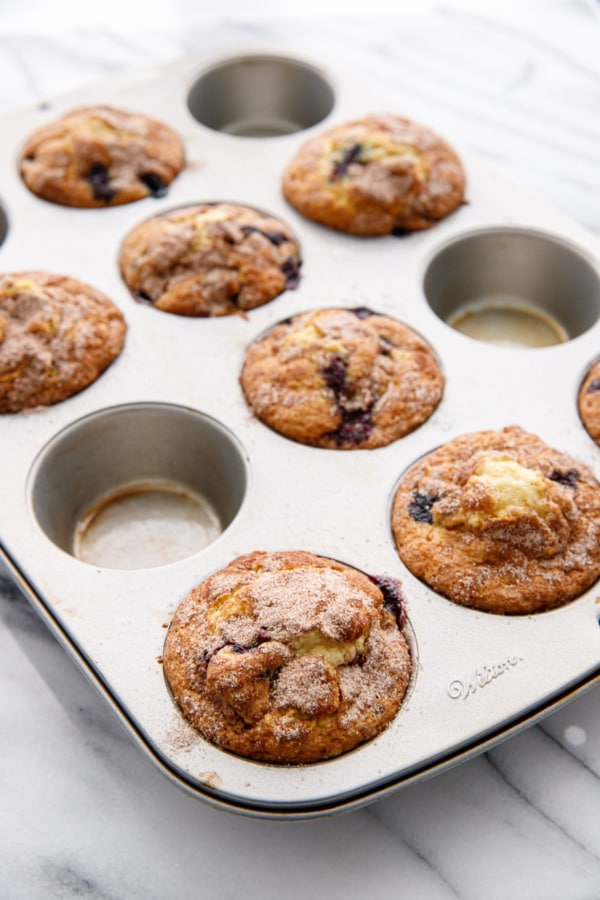 Silver muffin tin with blueberry muffins on a marble background