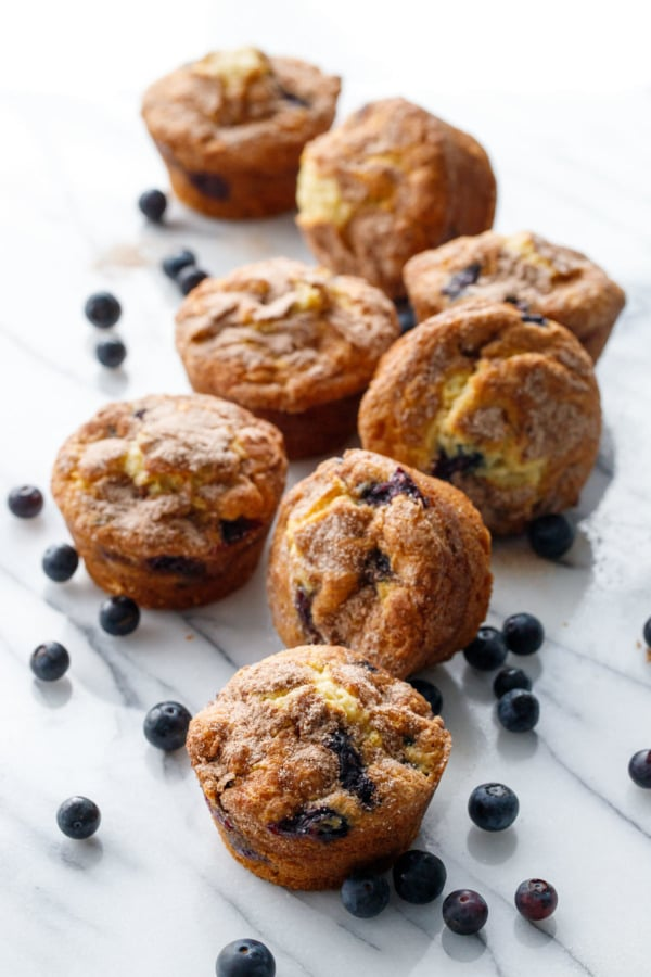 Scattered blueberry muffins and loose blueberries on a marble background