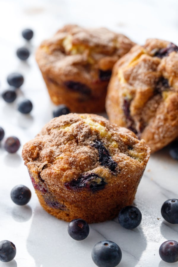 Blueberry muffins on a marble background, with fresh blueberries scattered around.