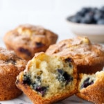 Split blueberry muffin to show inside texture, on marble with more muffins and blueberries in the background