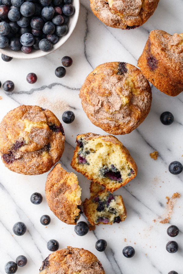 Overhead of scattered muffins and blueberries on marble, one muffin split in half to show the fluffy texture.