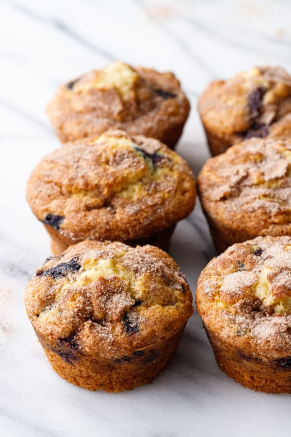 Two rows of blueberry muffins on a marble background
