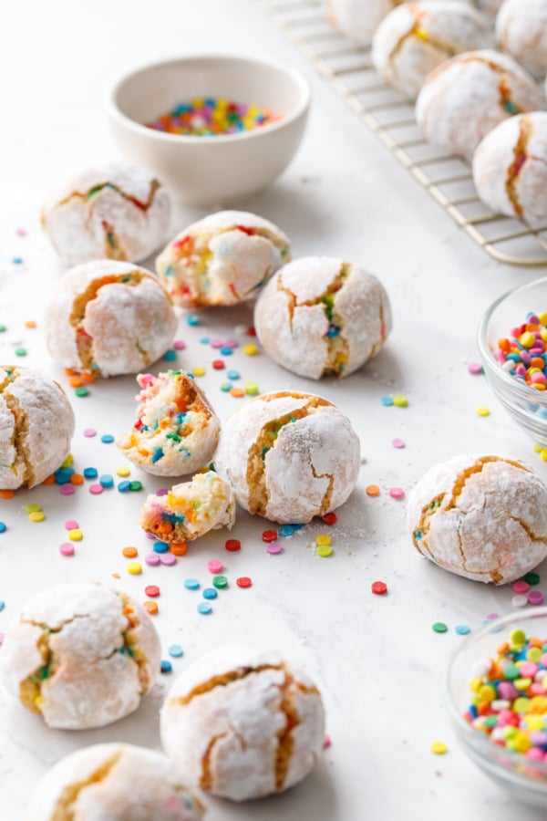 Whole and broken confetti amaretti cookies with a bowl of sprinkles and more scattered around