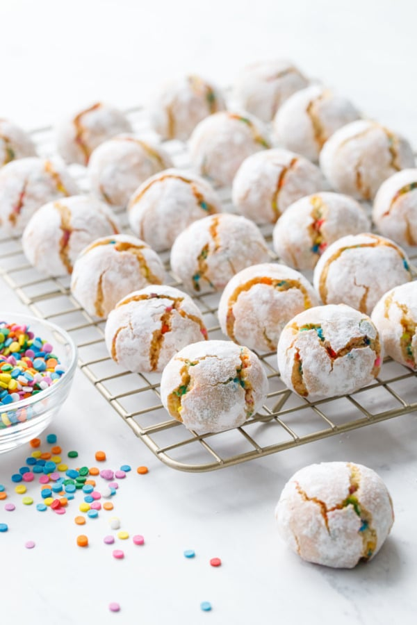 Confetti amaretti cookies on a cooling rack with a bowl of rainbow sprinkles