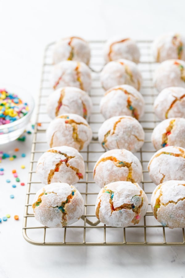 Rows of funfetti amaretti cookies on a cooling rack with a bowl of rainbow sprinkles