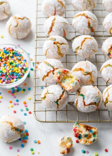 Messy arrangement of funfetti amaretti cookies with broken and bitten into cookies to show texture