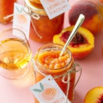 Open jar of peach jam with a gold spoon, on a pink background with more jars of jam, cut peaches and a glass of bourbon.