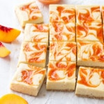 Peach cheescake bars cut into squares, arranged on a piece of crinkled parchment with a bowl of peach puree and a few peach slices scattered around.