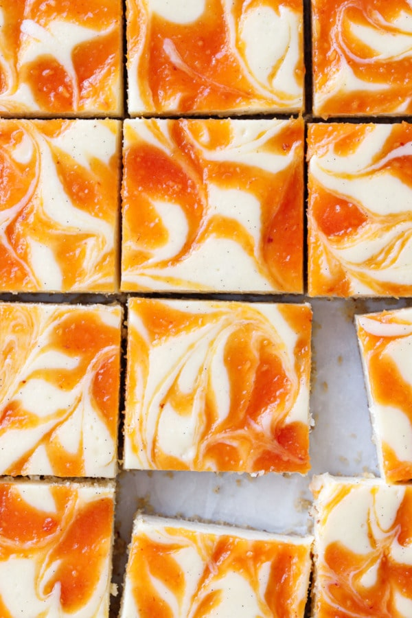 Close up overhead view of sliced peach swirl cheesecake bars, with a few bars slightly offset from grid