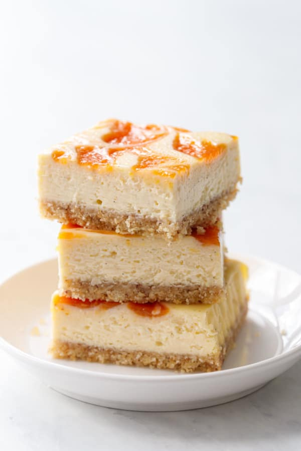 Stack of three squares of peach cheesecake bars, showing the texture of the cheesecake filling and glossy reflection off the swirl of peach baked on top.