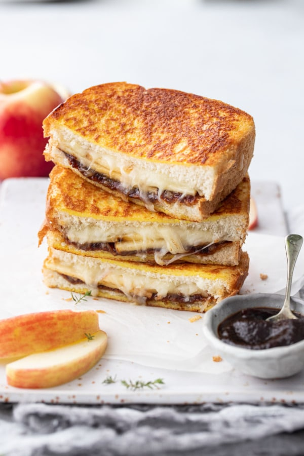 Stack of apple butter grilled cheese halves on a rectangular plate