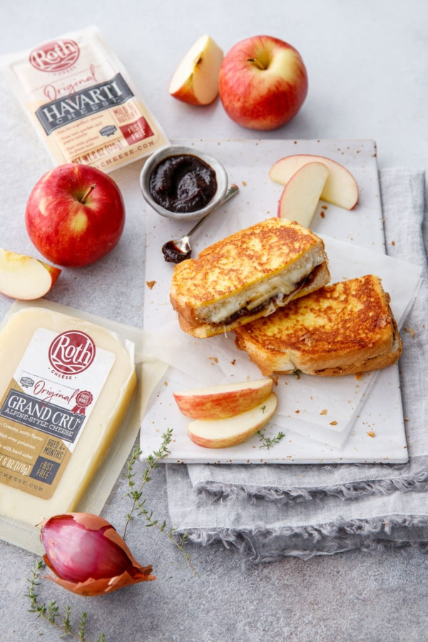 Apple butter grilled cheese cut in half on a plate, with raw ingredients around it.