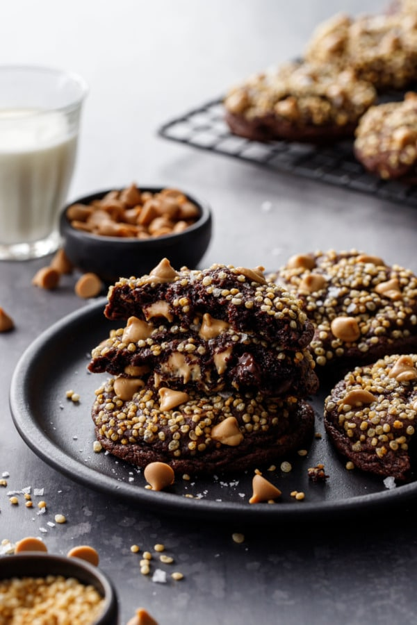 Chocolate cookies topped with puffed quinoa, on a plate with a glass of milk