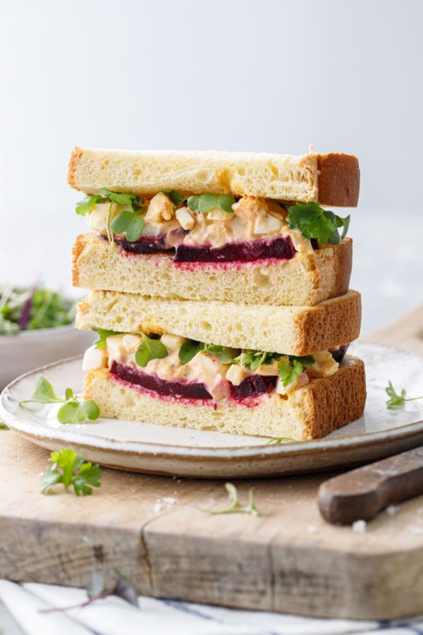 Sandwich cut in half and stacked showing layers of beet and egg salad